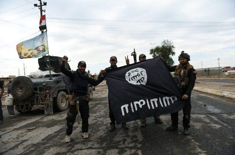 Iraqi soldiers pose with a captured Islamic State group flag in the village of Gogjali near Mosul's eastern edge, on November 2, 2016