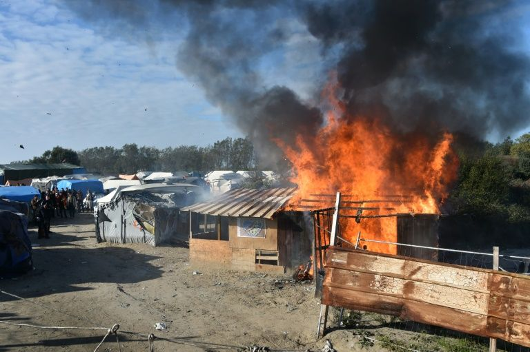 "A shack is set on fire during the demolition of the ""Jungle"" migrant camp in Calais, northern France, on October 25, 2016"