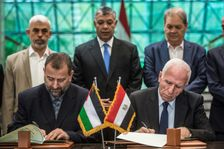 Fatah's Azam al-Ahmad (R)and Saleh al-Aruri (L) of Hamas sign a reconciliation deal at the Egyptian intelligence services headquarters in Cairo on October 12, 2017
