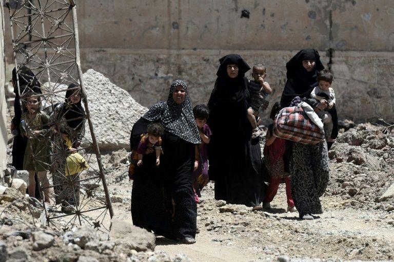 نازحات عراقيات غادرن منازلهن في حي الشفا غرب الموصل، يسرن مع اطفالهن باتجاه القوات العراقية خلال عمليات استعادة المدينة من الجهاديين، الخميس 17 حزيران/يونيو 2017