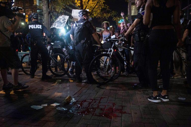 Des manifestants et forces de police autour d'une tache de sang sur le sol lors d'une manifestation contre les violences policières à Charlotte (Caroline du Nord), le 21 septembre 2016