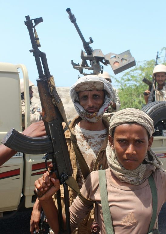 Forces loyal to the Saudi-backed Yemeni president show off their weapons on a road in Abyan province on April 23, 2016