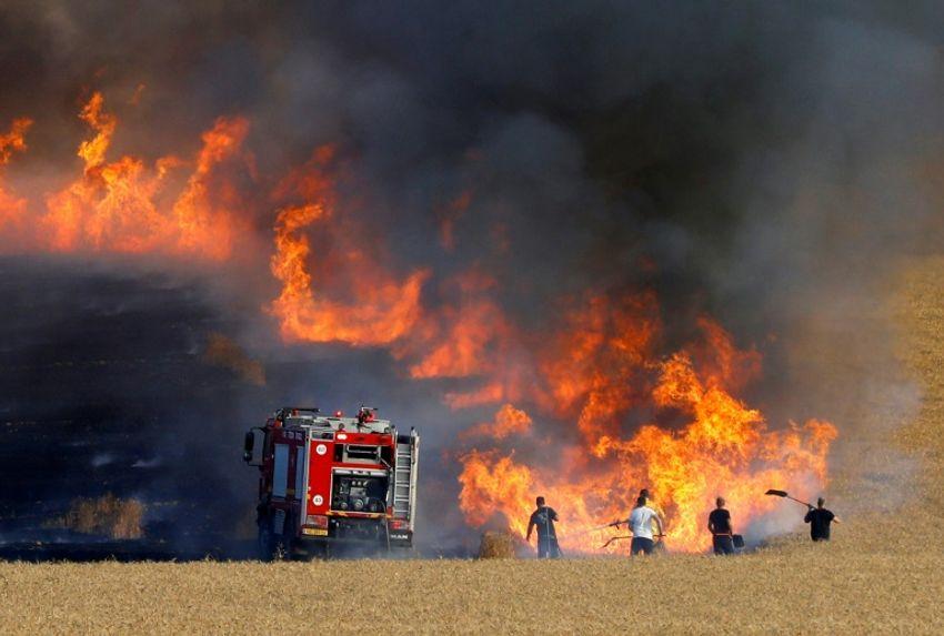 Des pompiers israéliens tentent d'éteindre l'incendie d'un champs proche de à la frontière avec la bande de Gaza, le 15 mai 2018