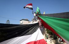 Palestinians wave flags as they gather in Gaza City to celebrate after rival Palestinian factions Hamas and Fatah reached an agreement on ending a decade-long split following talks mediated by Egypt on October 12, 2017