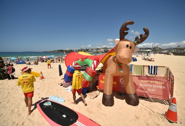 Surf lifesavers (L) walk past a Christmas tree and an inflatable reindeer on Bondi Beach on Christmas Day in Sydney