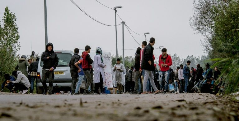 Migrants stand in the 'Jungle' migrant camp, in Calais, northern France, on November 1, 2016, a day after a massive operation to clear the squalid settlement where 6,000-8,000 people have been living in dire conditions