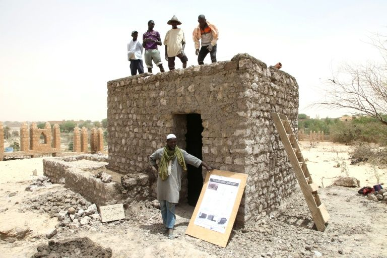 Workers pose during the reconstruction of a mausoleum in the Three Saints cemetery on April 8, 2015 in Timbuktu, northern Mali
