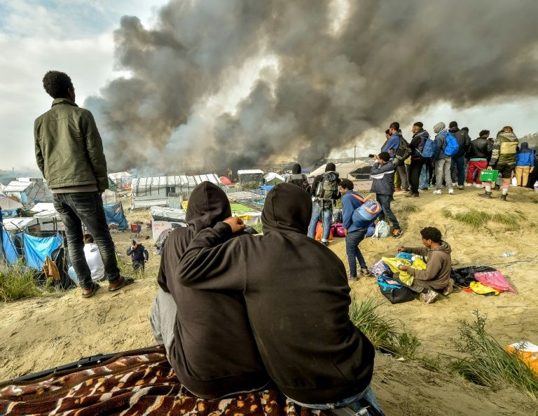 "Migrants looks at the smoke rising from fires in the ""Jungle"" migrant camp in Calais on October 26, 2016"