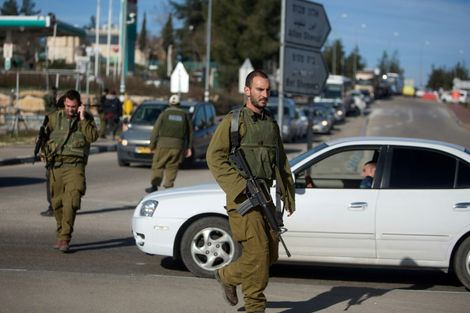 Israeli soldiers stand guard at the Gush Etzion junction in the West Bank on January 5, 2016