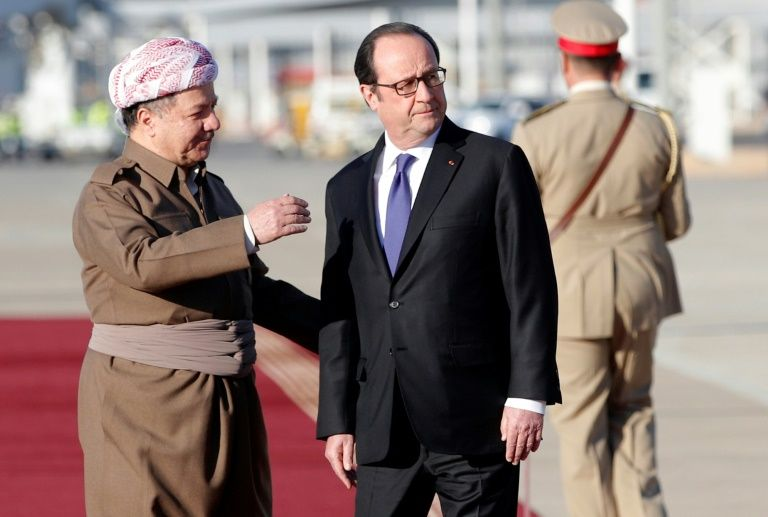 French President Francois Hollande (R) is greeted by Iraqi Kurdish leader Massud Barzani (L) during a ceremony in the International Airport of Arbil