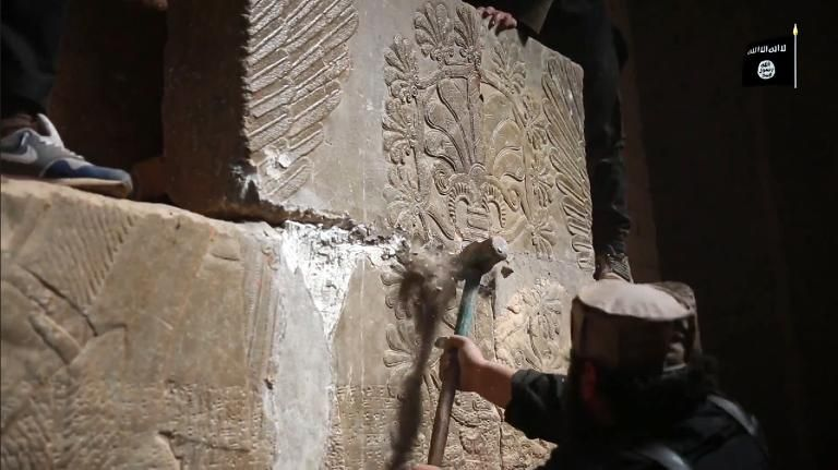 Members of the Islamic State militant group are allegedly shown destroying a stoneslab with a sledgehammer in the ancient Assyrian city of Nimrud in northern Iraq, in this screen grab from a Welayat Nineveh video on April 11, 2015