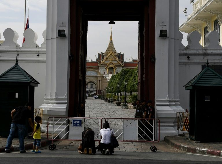 Women pay their respects to the late Thai King Bhumibol Adulyadej outside the Grand Palace in Bangkok