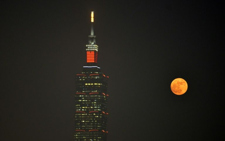 "A ""supermoon"" rises next to the Taipei 101 building, a 508-meter high skyscraper, in Taipei on November 14, 2016"