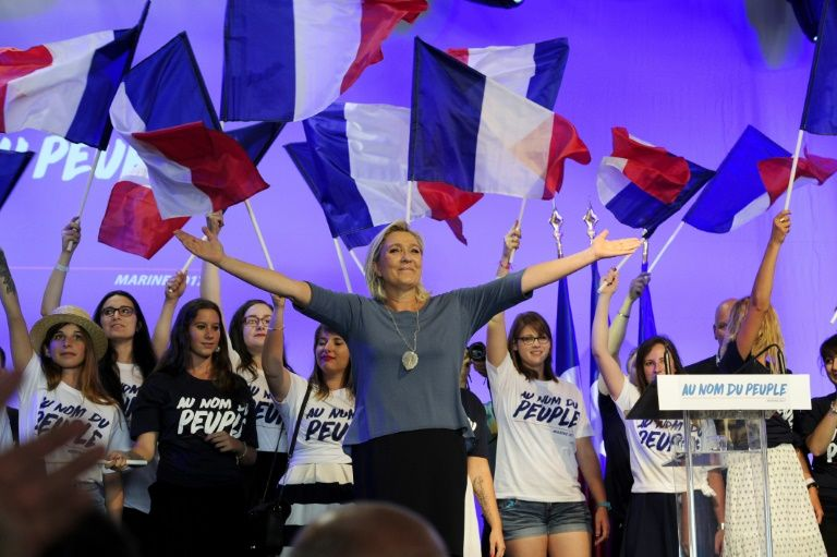 French far-right Front National (FN) party's President, Marine Le Pen, acknowledges the audience on stage during the FN's summer congress