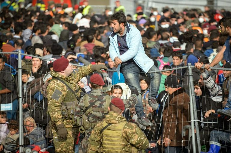 A migrant tries to overpass the fence, as migrants and refugees wait to cross the Slovenian-Austrian border, from the Slovenian city of Sentilj, on October 30, 2015