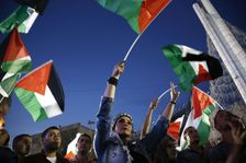 Palestinians wave their national flags as they watch a live-screening of president Mahmud Abbas' speech followed by the raising of the Palestinian flag at the United Nations headquarters in New York, on September 30, 2015 in the city of Ramallah