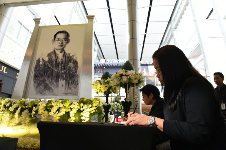 A Thai woman signs a condolence book near an image of the late Thai King Bhumibol Adulyadej at a mall in Bangkok