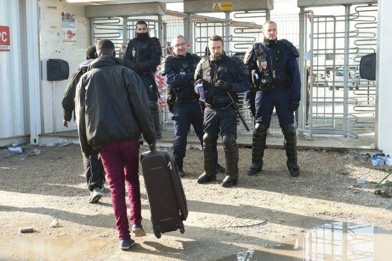 "Un migrant se dirige vers des policiers à l'entrée de la ""Jungle"" de Calais, le 23 octobre 2016"