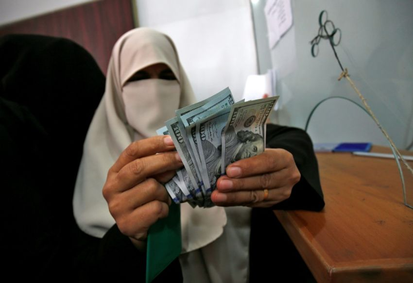 A Palestinian woman counts her money after receiving her salary in Rafah in the southern Gaza Strip on November 9, 2018