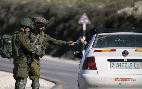 Israeli soldiers check the ID of a Palestinian driver at a checkpoint in the West Bank on January 11, 2018