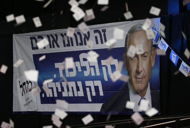Confetti falls in front of a poster of Israeli Prime Minister Benjamin Netanyahu as supporters of his Likud party wait for election results