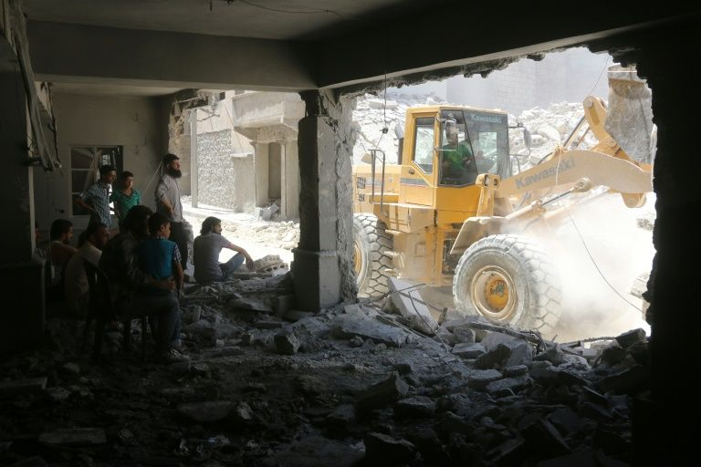 Syrians shelter in a damaged building as civil defence workers sift through debris looking for survivors following reported air strikes on July 14, 2016 in Aleppo's rebel-held neighbourhood of Tariq al-Bab