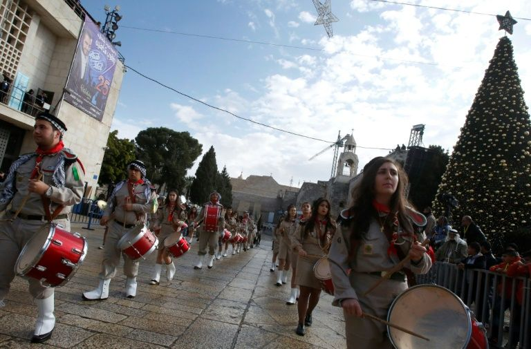 Palestinian Christian scouts perform at Manger Square outside the Church of the Nativity in Bethlehem on December 24, 2016 as people gather for Christmas celebrations in the city in the Israeli-occupied West Bank