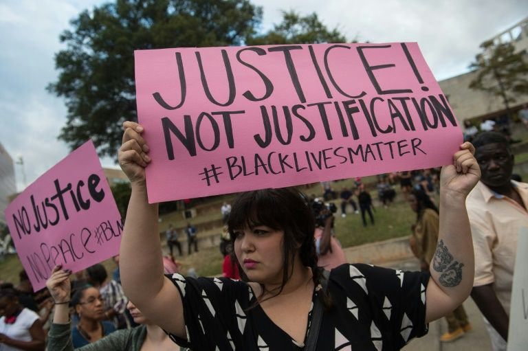Protesters hold up signs during a demonstration against police brutality in Charlotte, North Carolina, on September 21, 2016