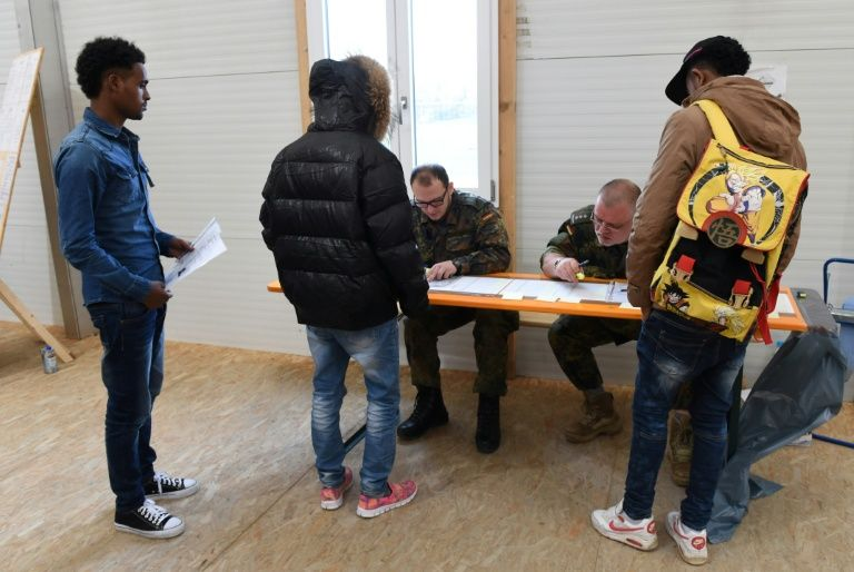 Newly arrived migrants line up at a registration point in Erding near Munich, southern Germany, on November 15, 2016