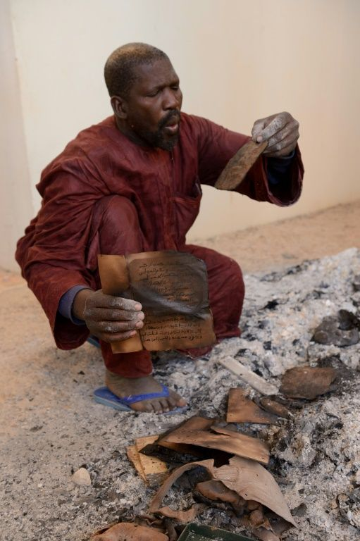 A man recovering burnt ancient manuscripts at the Ahmed Baba Centre for Documentation and Research in Timbuktu