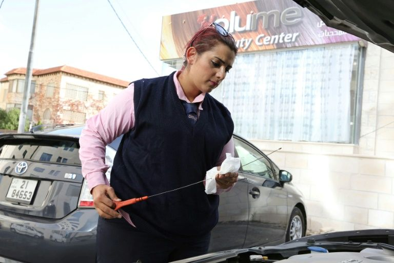 Nisrine Akoubeh checks the oil level of her taxi in Amman on 6 December 2016