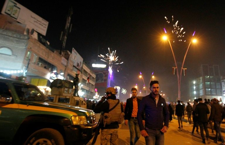 Iraqi walk past security forces as they gather at the al-Mansour square during Christmas and New Years eve celebrations in the capital Baghdad on December 31, 2016