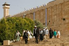 Tourists walk past Israeli flags hanging from the walls of the shared religious site -- known to Jews as the Cave of the Patriarchs and to Muslims as the Ibrahimi Mosque -- in the divided West Bank city of Hebron, in May 2016