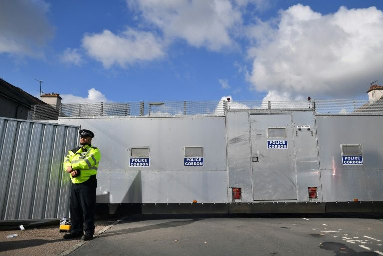 The metal fence set up by police around the house where an 18-year-old suspect in the London bombing of an Underground station lived in Sunbury, England