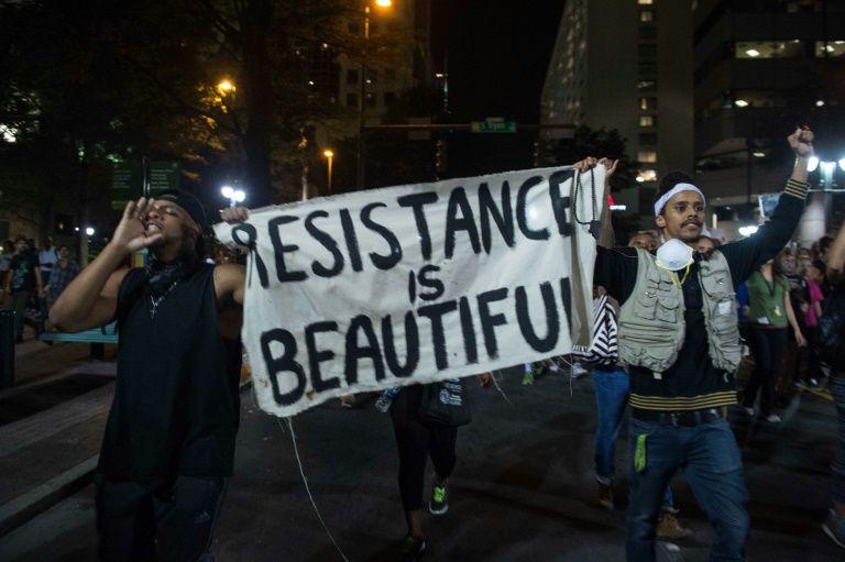 Deux manifestants défilent malgré le cessez-le-feu le 22 septembre 2016 dans la ville américaine de Charlotte