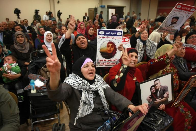 Relatives of Palestinian prisoners held in Israeli prisons hold portraits of their loved-ones and flash the sign for victory as they demonstrate in the West Bank city of Ramallah on March 27, 2014