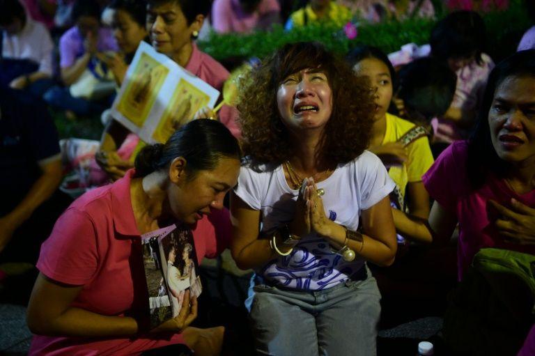 People react to the death of King Bhumibol Adulyadej outside the Siriraj Hospital in Bangkok, on October 13, 2016