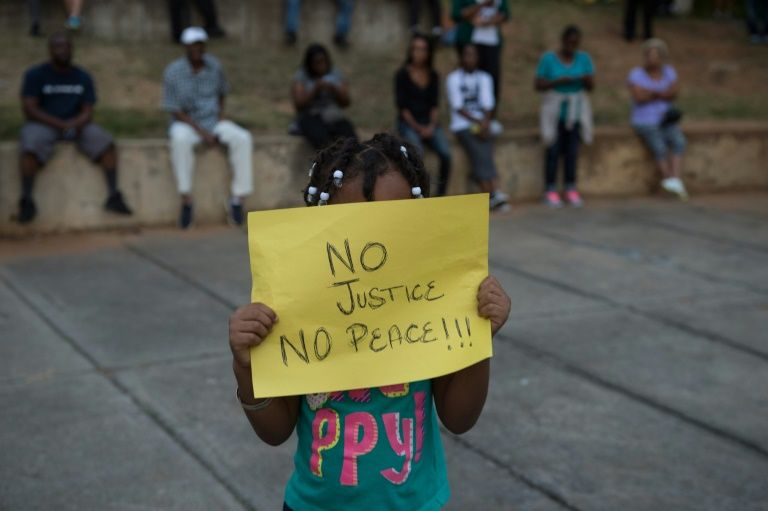 A little girl holds up a sign during a demonstration against police brutality in Charlotte, North Carolina, on September 21, 2016