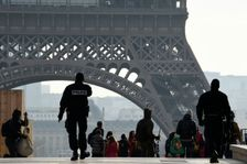 French police officers patrol around the Eiffel Tower in Paris on December 24, 2015