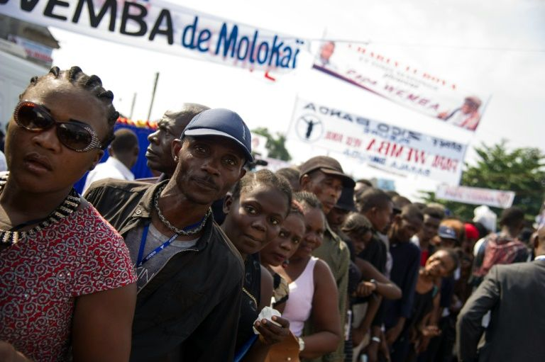 People gather in the streets of 'Village Molokoi' in the Matonge neighborhood of Kinshasa to pay tribute to late rumba musician Papa Wemba on May 2, 2016
