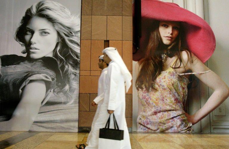 اماراتيان يمران امام لوحات اعلانية في دبي في 9 اذار/مارس 2009