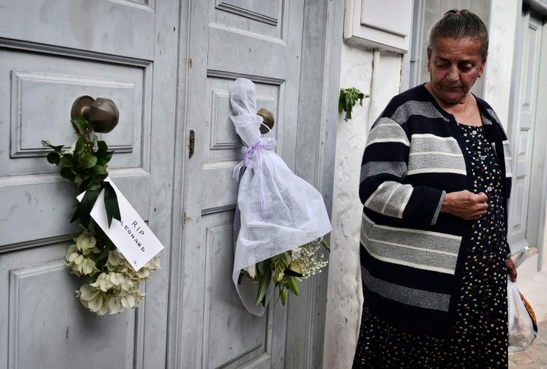 A former neighbour looks at flowers placed outside the summer house of late Canadian singer-songwriter and poet Leonard Cohen on the Greek island of Hydra, on November 12, 2016