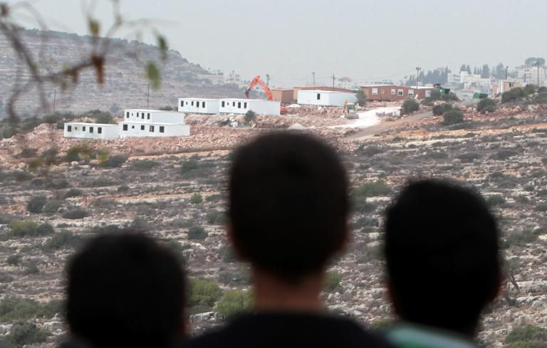 Palestinian children from the village of al-Mazraa al-Qabaliya look a bungalows in the distance built by Israeli settlers at an outpost constructed on land seized from the Palestinian village, near the West Bank city of Birzeit on December 3, 2013