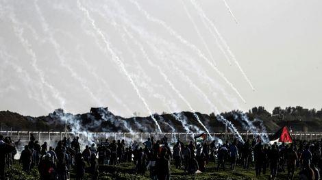Des manifestants palestieniens sous les tirs de gaz lacrymogènes lancés par des soldats israéliens postés à la barrière séparant Israël de la bande de Gaza, le 8 février 2019