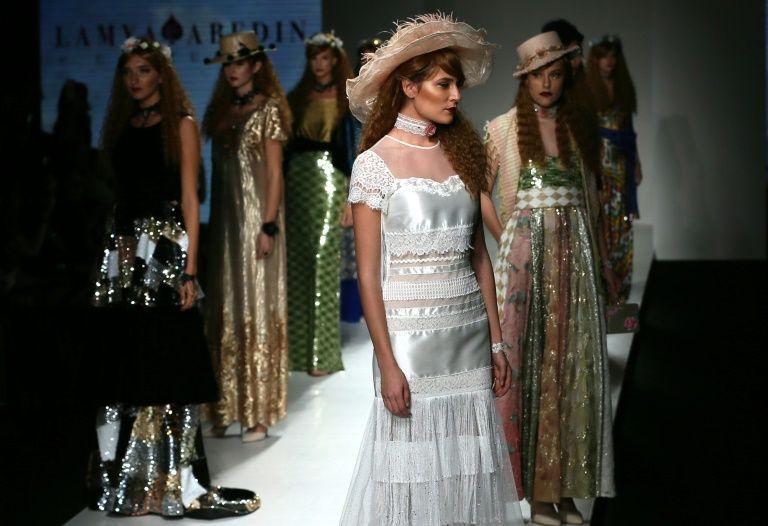Models present creations by Emirati fashion designer Lamya Abedin at the Arab Fashion Week in Dubai on October 6, 2016