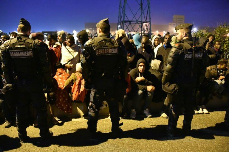 """Un cordon de policiers devant des migrants lors de l'évacuation de la """"Jungle"""" le 25 octobre 2016 à Calais"""