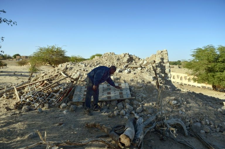 A man checks the ruins of the mausoleum of Alfa Moya, a Muslim saint, which was destroyed by Islamists in a cemetery of Timbuktu in 2013