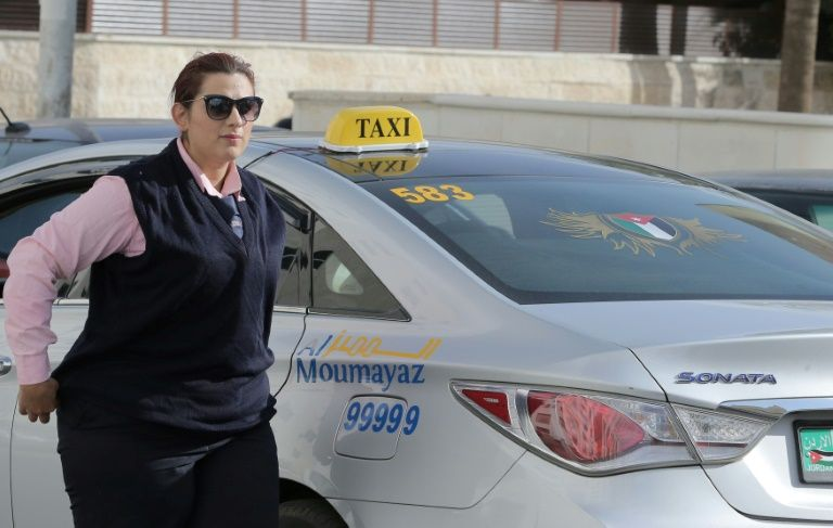 """Widow and former nurse Nisrin Akoubeh drives one of a fleet of 10 """"Pink Taxis"""" driven by women ... for women passengers, challenging Jordan's social norms"""