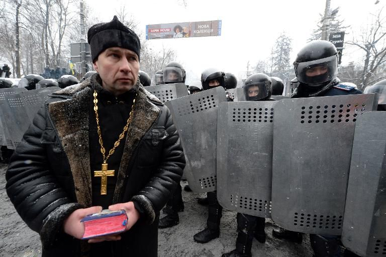 A Ukrainian priest walks past riot police in the center of Kiev, on January 22, 2014