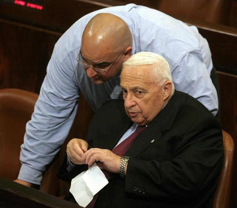 Israeli Prime Minister Ariel Sharon (R) listens to his son Omri during a Knesset (Israeli Parliament) session in Jerusalem on January 10, 2004
